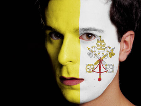 Flag of Vatican City Painted on a Face of a Young Man photo