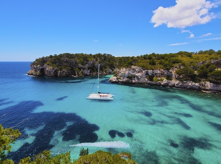catamaran: Catamaran in Cala Macarella on Menorca, Balearic Islands, Spain Stock Photo