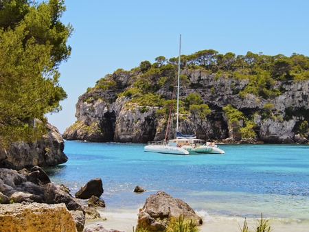 Catamaran in Cala Macarella on Menorca, Balearic Islands, Spain Reklamní fotografie