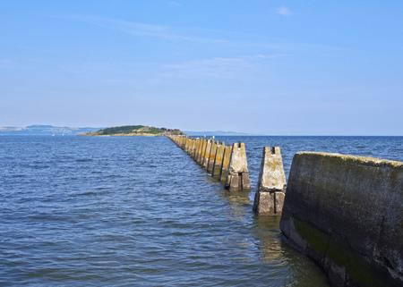 high tide: UK, Scotland, Lothian, Edinburgh Area, Cramond, Causeway and Pylons leading to the Cramond Island at high tide.  Stock Photo