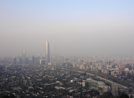 mundo contaminado: Chile, Santiago, View from the Parque Metropolitano towards the high raised buildings with Costanera Center Tower, the tallest building in South America. Heavy smog over the city.