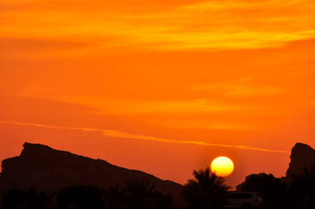 Sunset in Eastern Province. A colourful sky above the peaks of the Hajar Mountains, near Al Ain, UAE, part of the Hajar range Stock Photo
