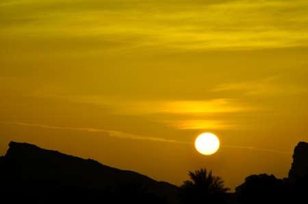 Sunset in Eastern Province, Abu Dhabi. A colourful sky above the peaks of the Hajar Mountains, near Al Ain, UAE, part of the Hajar range