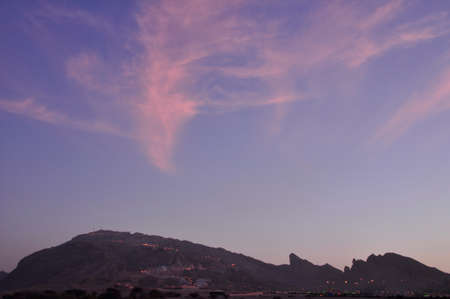 The skies above Jebal Hafeet. A colourful sky above the peaks of the Hajar Mountains, near Al Ain, UAE, part of the Hajar range Stock Photo