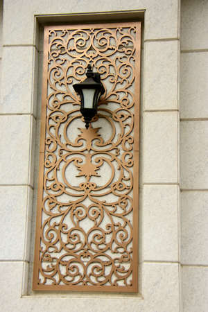 Wall light. A light fixture mounted on a decorative wall panel