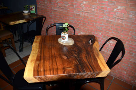A wooden table cut from a broad tree trunk and used in a restaurant in Georgetown, Malaysia