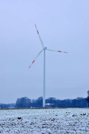 Tall wind generators producing renewable clean electrical energy, here in the German countryside