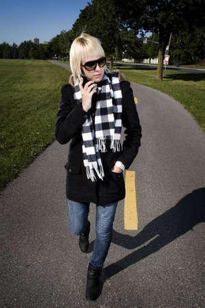 Girl walking along bike path calling someone photo