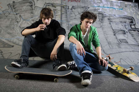 skateboarding: Two skateboarders sitting on ramp in skatepark