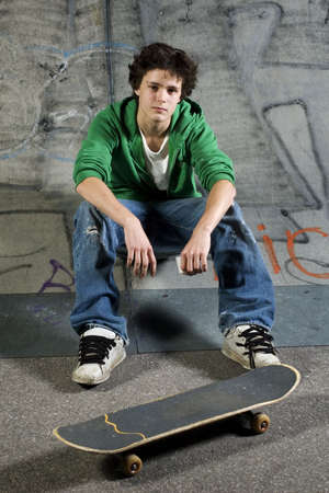 Young skateboarder looking at camera sitting on ramp photo
