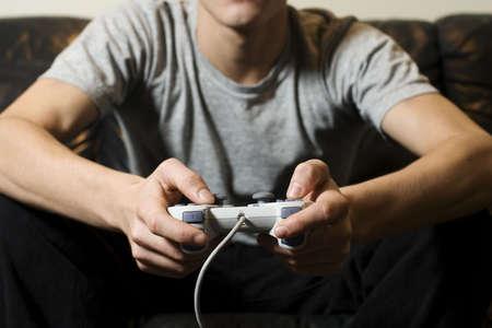 jugando videojuegos: Joven celebraci�n de control de video juego Foto de archivo
