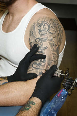 tattoo arm: Arm of man getting tattooed in tattoo shop Stock Photo