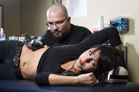 rib cage: Woman getting tattooed on rib cage in tattoo shop