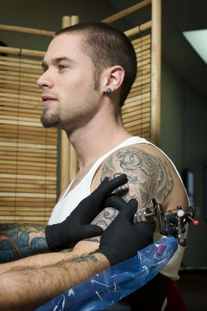 Young man getting tattooed on his arm in tattoo shop photo