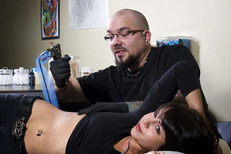 stab: Tattoo artist about to stab his client in tattoo shop