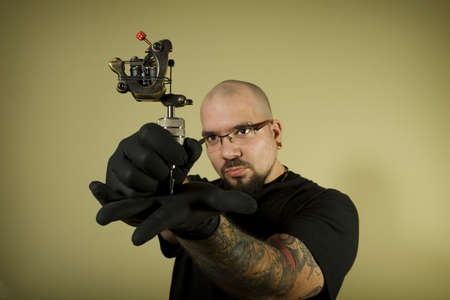 machines: Portrait of tattoo artist holding his machine