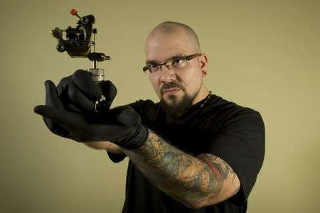 Portrait of tattoo artist holding his machine photo