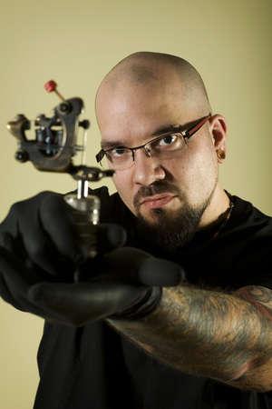 Portrait of tattoo artist holding his machine (vertical) photo