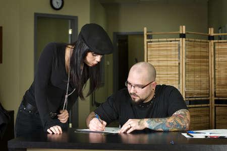 Tattooer preparing tattoo for client in tattoo shop photo