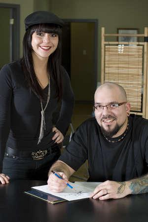 Tattooer preparing tattoo for happy client in tattoo shop photo
