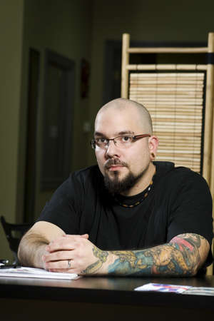 Owner of tattoo parlor sitting at desk in tattoo shop photo
