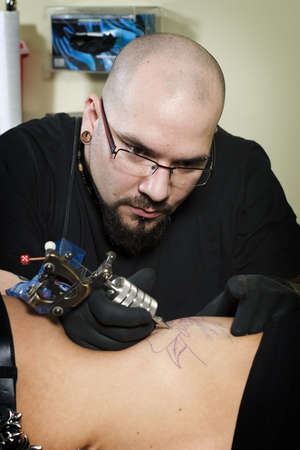 Tattooing on the side of clients abdomen in tattoo shop photo