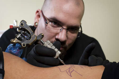 rib cage: Tattooer concentrating on performing a tattoo on a clients rib cage