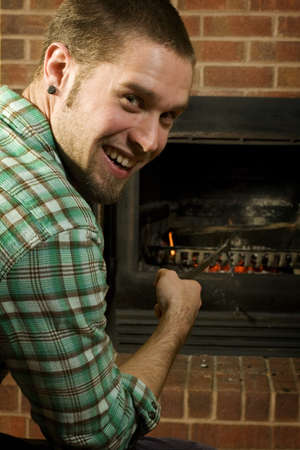 poking: young man poking at fireplace inside home