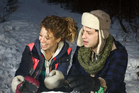 looking away from camera: Beautiful couple playing in snow looking away from camera