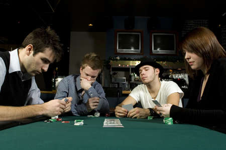 card player: Four friends playing poker together in bar