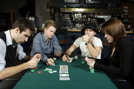 card game: Four friends playing poker around table in bar