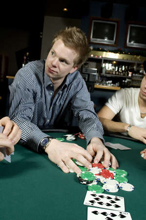 all in: Young man taking his poker winnings after going all in
