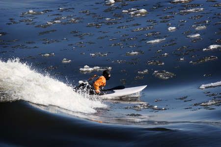 icey: Daring surfer surfing in winter on wave