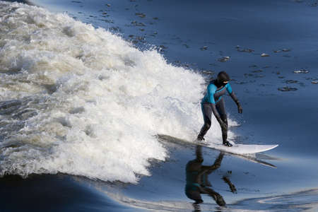 icey: Woman in full body wet suit riding wave Stock Photo