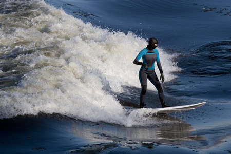icey: Femal surfer in full body wet suit riding wave Stock Photo