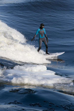 icey: Female surfer riding wave with iceberg beside