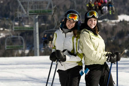 Two beautiful girls skiing together on mountain slopes