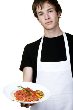 plate: Isolated young cook holding plate of linguine with tomato sauce