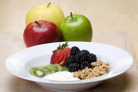 Fresh fruit with yogurt and granola on plate photo