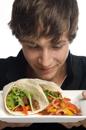 Young man smelling plate of fresh and delicious tacos