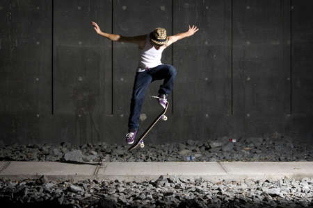 Skateboarder doing an ollie on walking path with concrete wall behind
