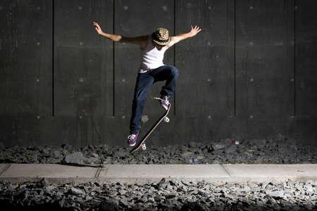 stunts: Skateboarder facendo un ollie sul sentiero con un muro di cemento dietro Archivio Fotografico