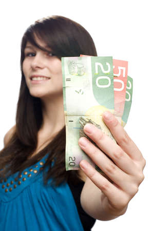 Young beautiful woman holding canadian currency smiling  Stock Photo