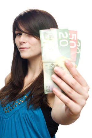 canadian currency: Young beautiful woman holding canadian currency smiling