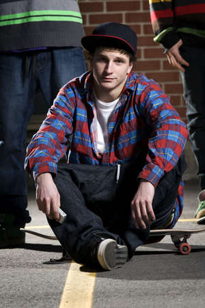 Skateboarder sitting on his board with friends behind photo