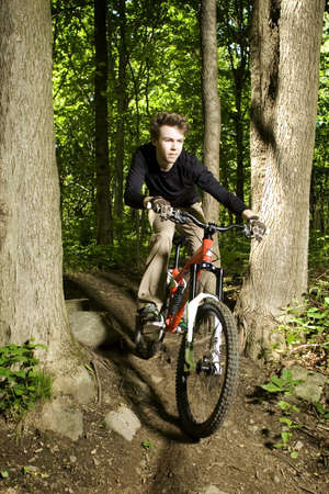 Mountain biker riding through trees downhill photo