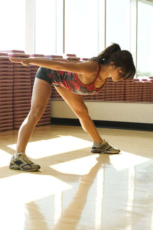 working woman: Young woman stretching in work out room