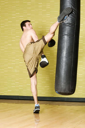 Kickboxer working out on punching bag photo
