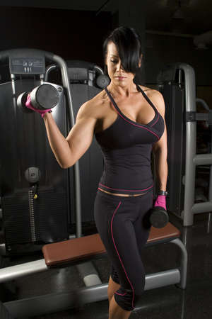 Asian woman working out with weights in gym Stock Photo - 8256938