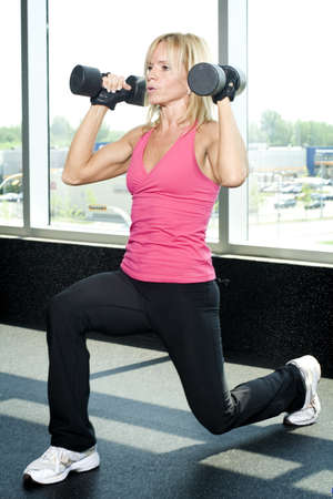Middle aged woman working out with weights